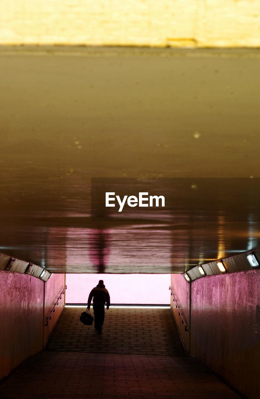 Rear View Of Man Walking At Underground Walkway