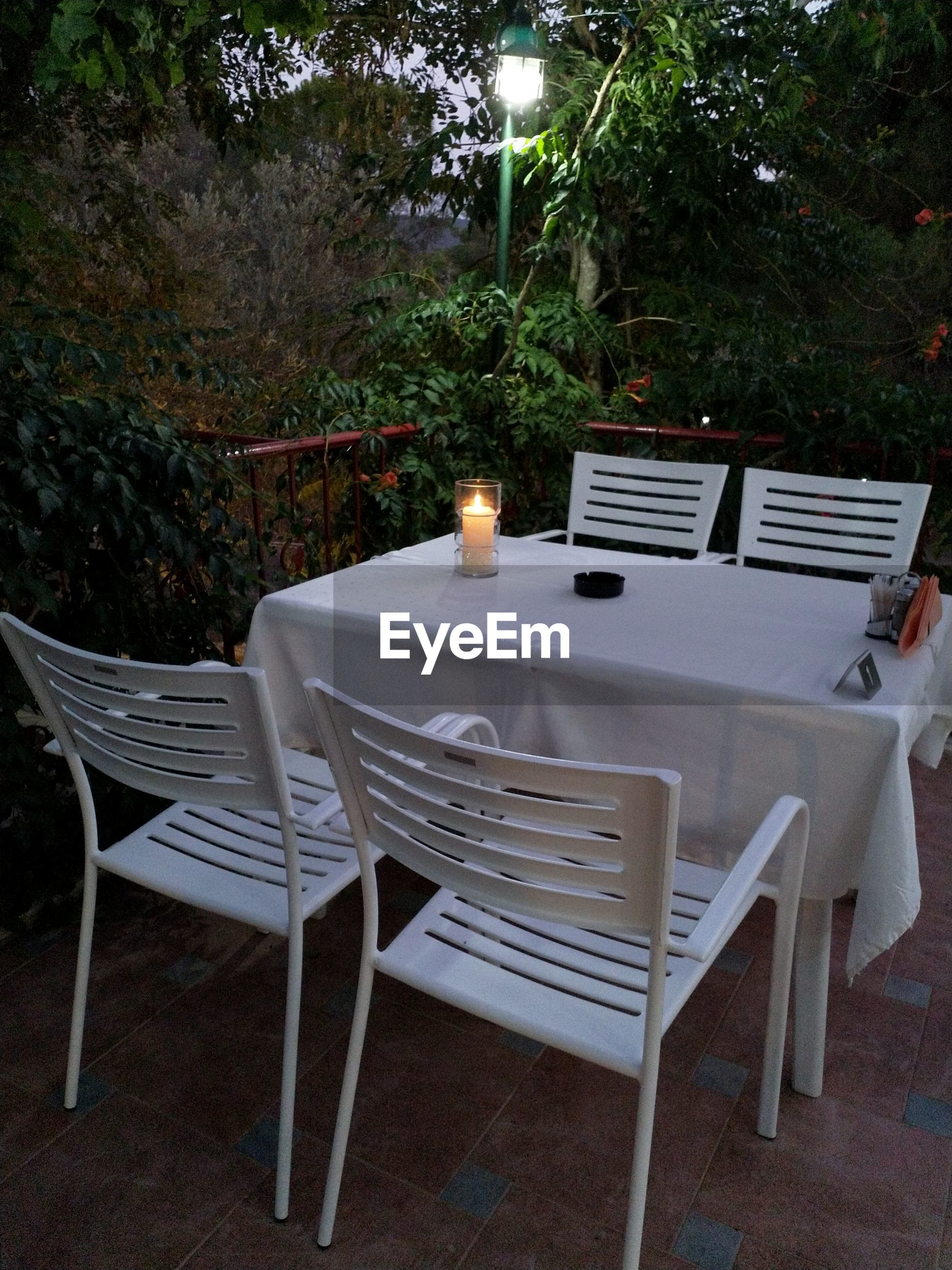 seat, chair, table, plant, no people, absence, food and drink, nature, restaurant, empty, candle, illuminated, lighting equipment, place setting, furniture, tree, night, setting, glass, outdoors, dining