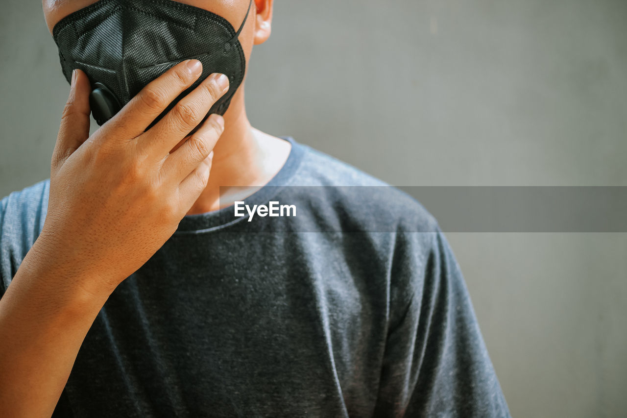 Midsection of mature man wearing pollution mask standing against wall