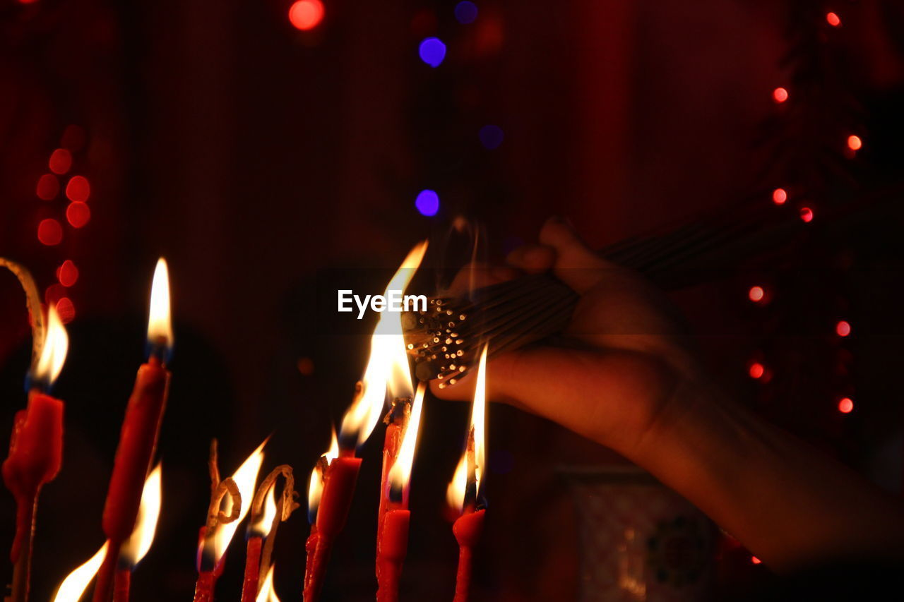 Cropped Hand Burning Incense Sticks At Temple