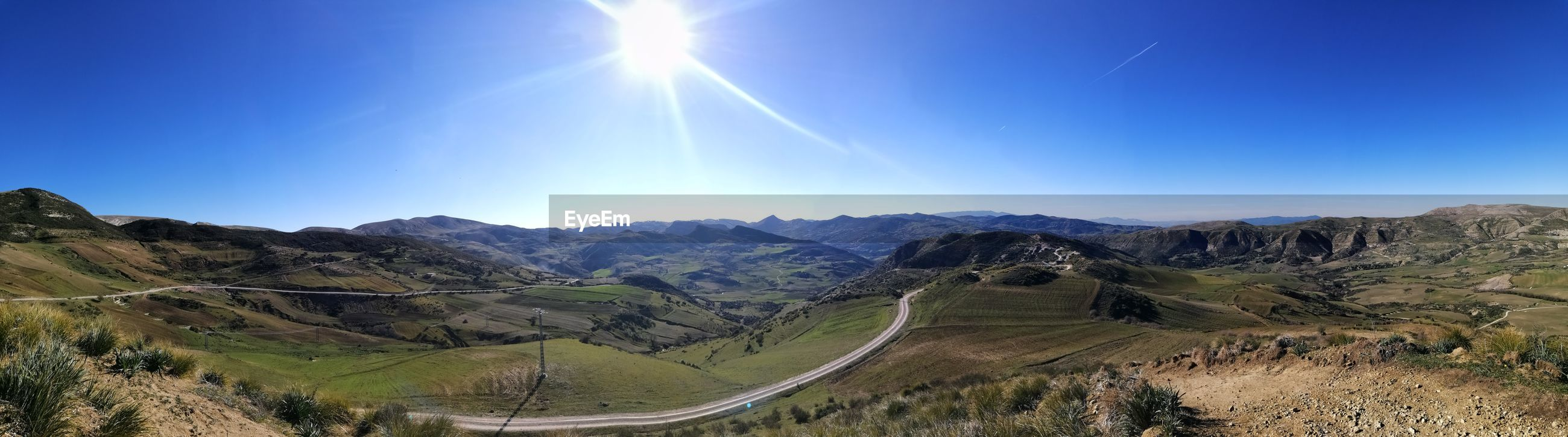 Panoramic view of mountains against blue sky on sunny day