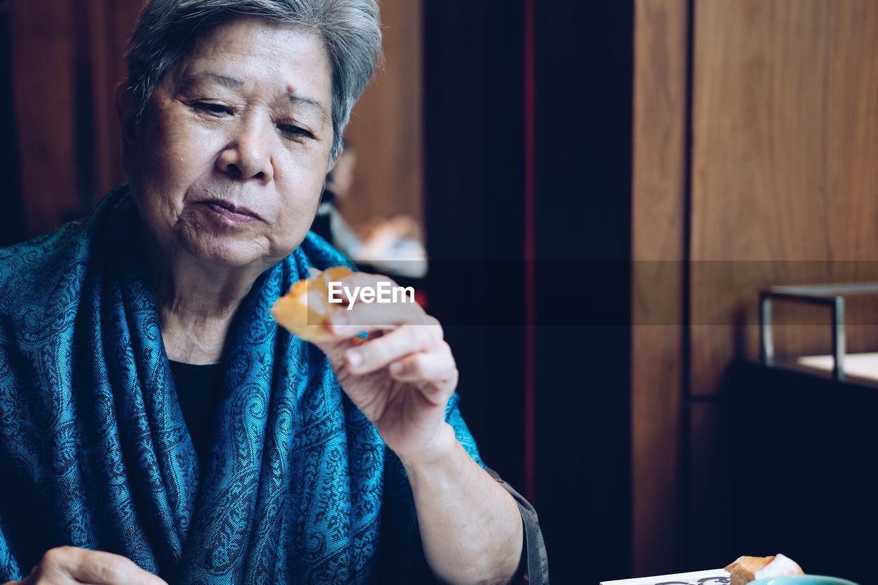 Senior woman eating breakfast at home