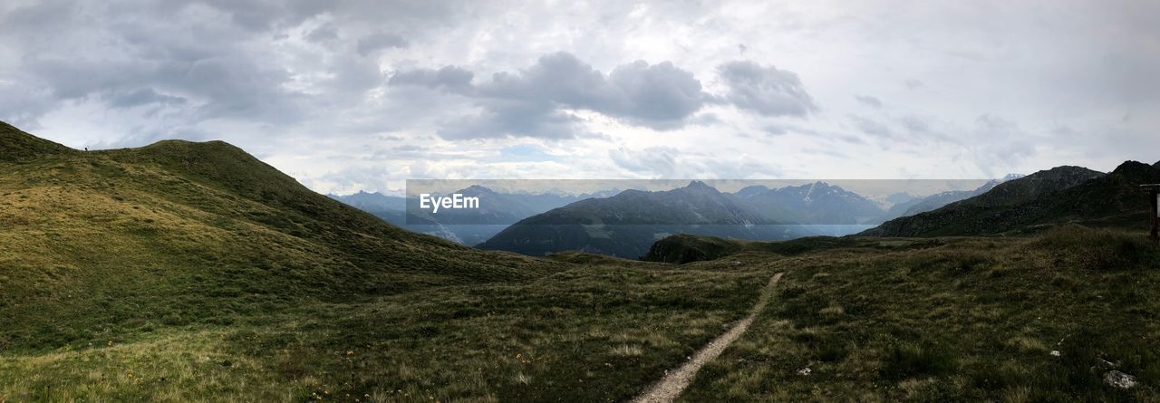 mountain, sky, environment, landscape, cloud - sky, nature, scenics - nature, beauty in nature, panoramic, no people, outdoors, mountain range, land, tranquil scene, wilderness, day, tranquility, valley, non-urban scene, grass, mountain peak, range