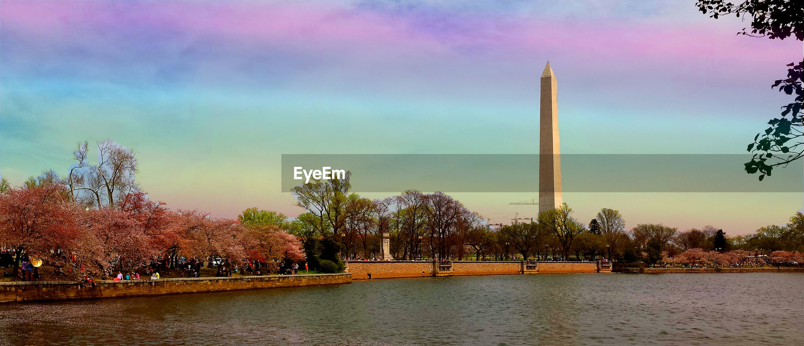 Washington monument by river against sky