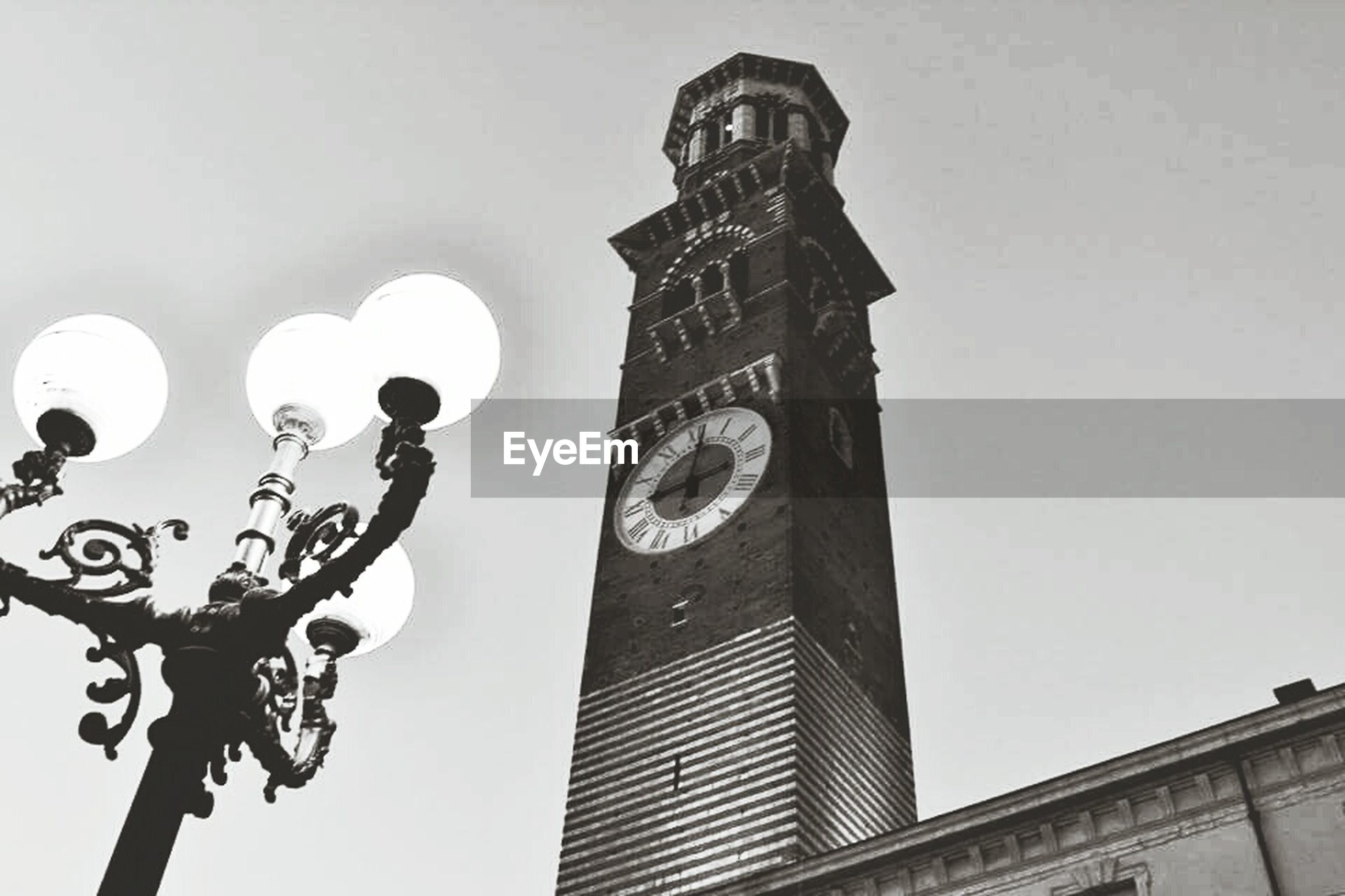 low angle view, architecture, built structure, building exterior, clear sky, street light, metal, day, communication, no people, time, lighting equipment, outdoors, clock, city, text, tower, building, wall - building feature, sky