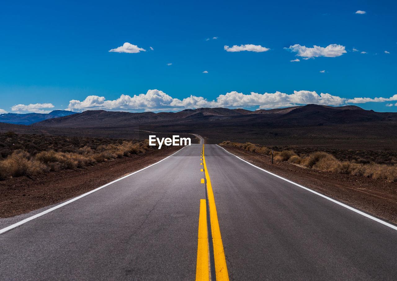 Road leading towards mountain range against blue sky