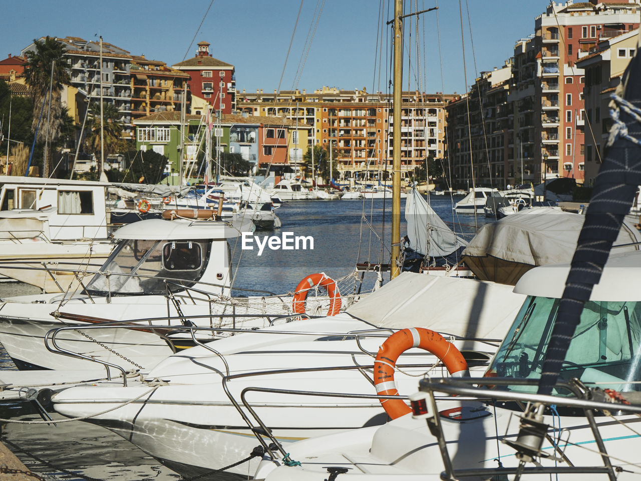 SAILBOATS MOORED IN HARBOR BY BUILDINGS IN CITY