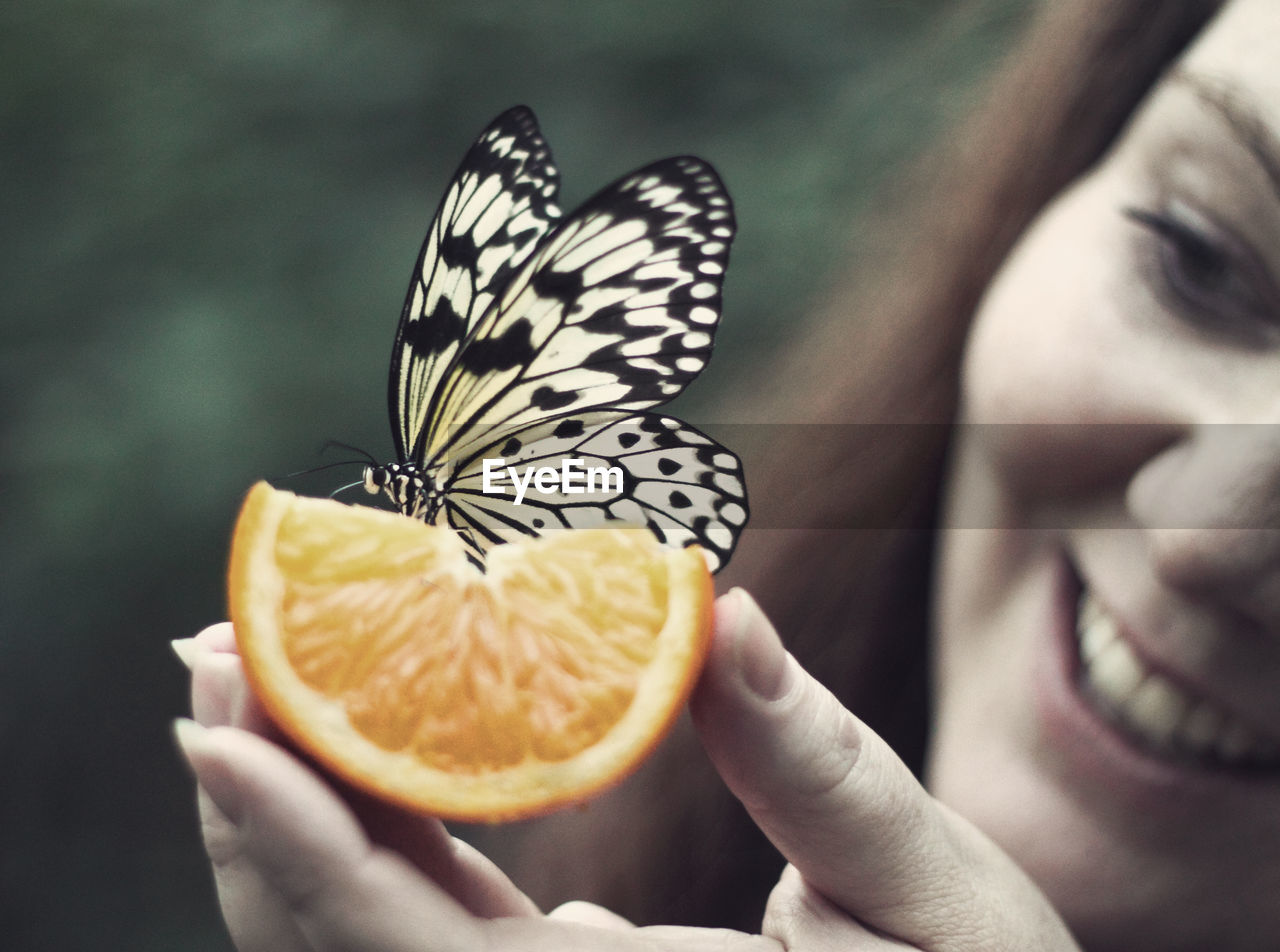 Cropped Image Of Smiling Woman Holding Orange With Butterfly On It