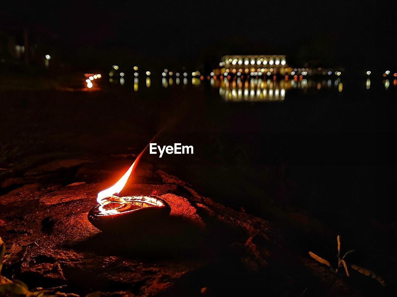 illuminated, night, flame, burning, fire, glowing, lighting equipment, nature, heat - temperature, no people, fire - natural phenomenon, focus on foreground, water, light - natural phenomenon, close-up, candle, oil lamp, architecture, outdoors, dark, electric lamp