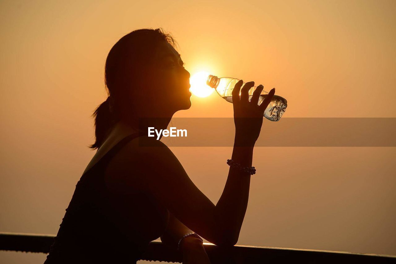 Side view of silhouette woman drinking water from bottle against orange sunset sky
