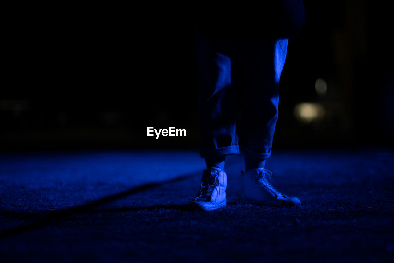 Low Section Of Person Standing On Footpath At Night