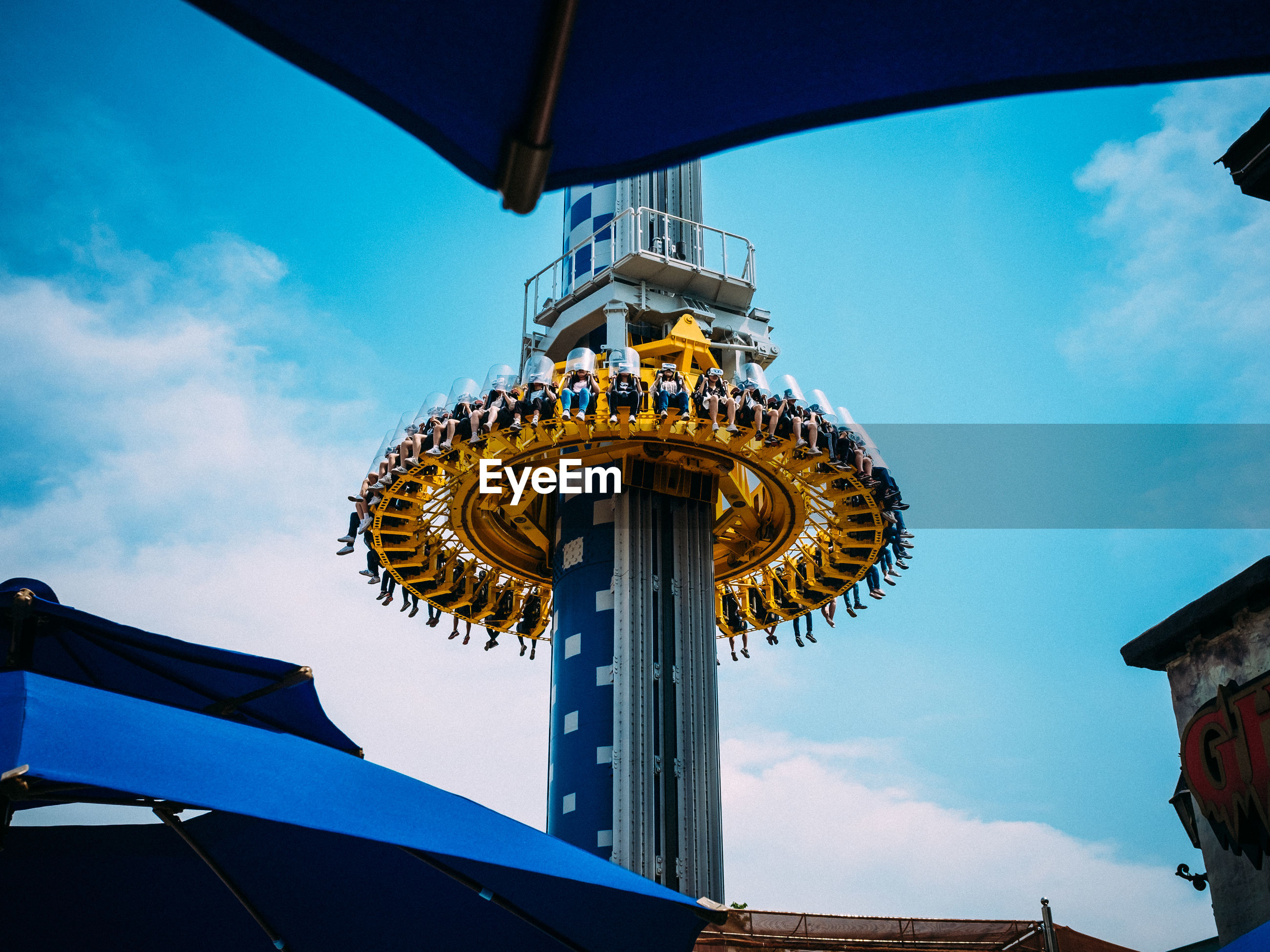 low angle view, sky, built structure, amusement park, cloud - sky, arts culture and entertainment, architecture, day, blue, amusement park ride, outdoors, building exterior, no people, carousel, nature