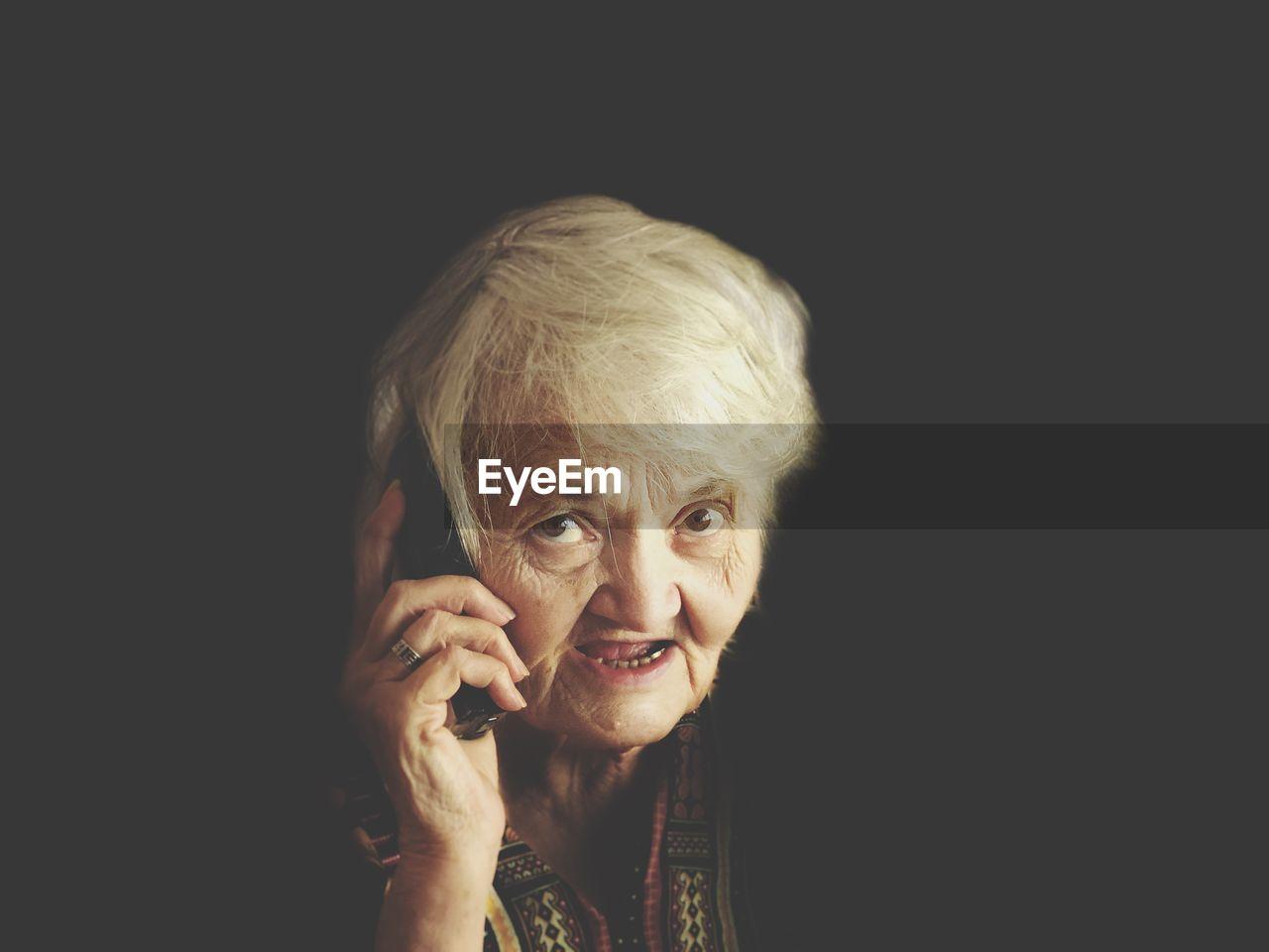 Portrait Of Senior Woman Talking On Smart Phone Against Black Background