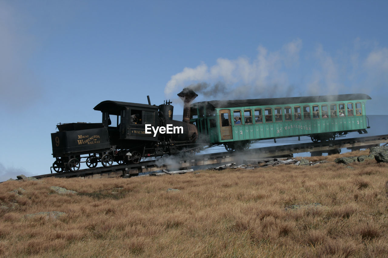 land, mode of transportation, sky, transportation, train, field, motion, smoke - physical structure, train - vehicle, day, steam train, nature, rail transportation, environment, land vehicle, outdoors, grass, no people, public transportation, on the move