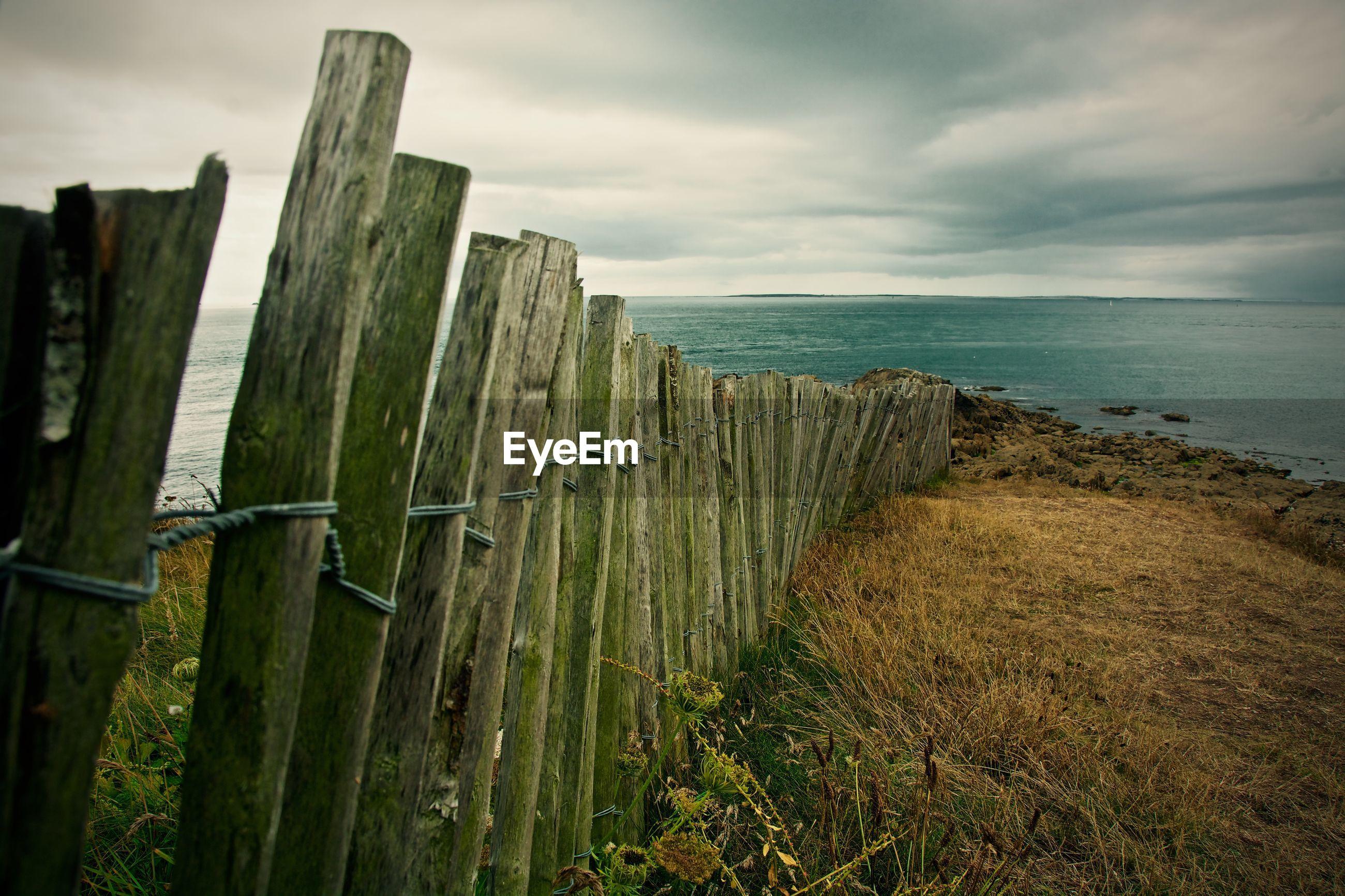 Wooden fence on beach against cloudy sky