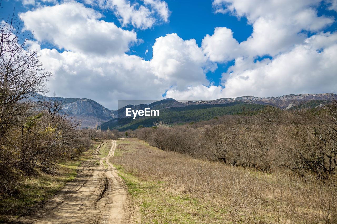 cloud - sky, sky, mountain, direction, beauty in nature, environment, tranquil scene, tranquility, scenics - nature, the way forward, road, landscape, non-urban scene, nature, mountain range, transportation, no people, plant, day, dirt road, outdoors, long, trail