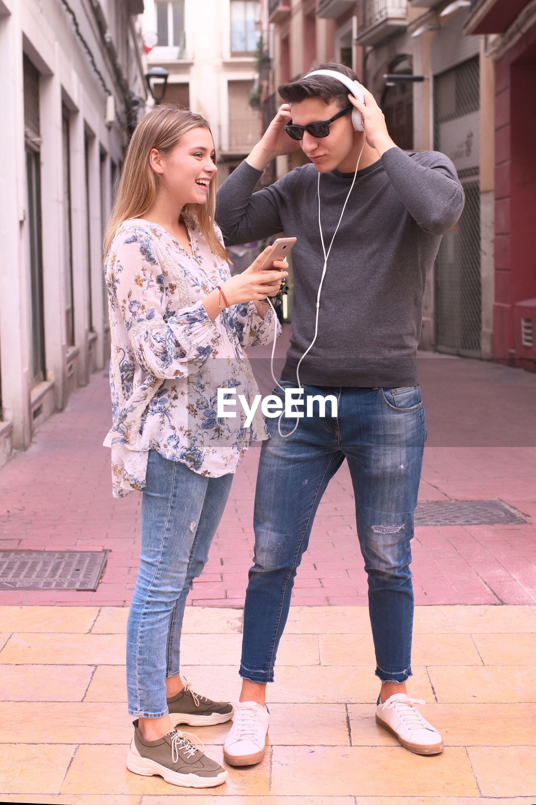 YOUNG COUPLE STANDING ON FOOTPATH