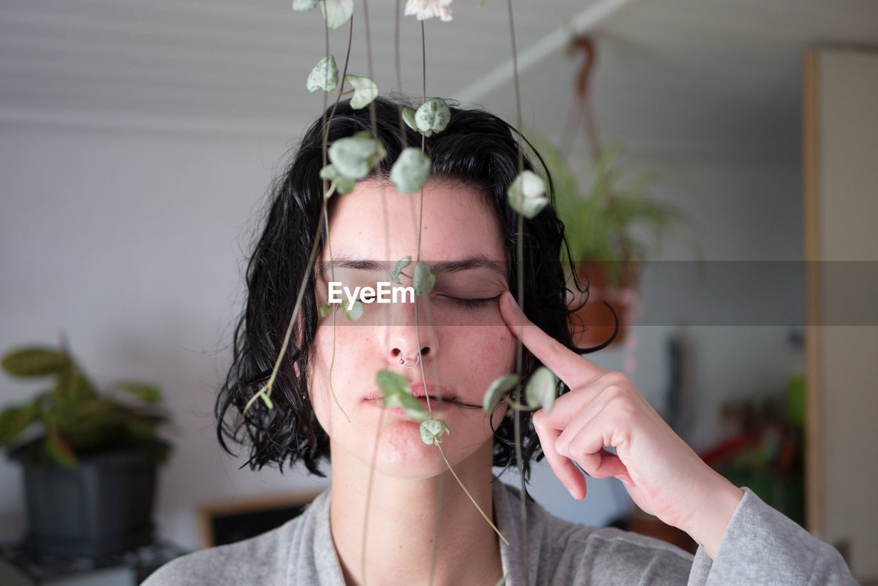 Woman With Closed Eyes By Plants At Home