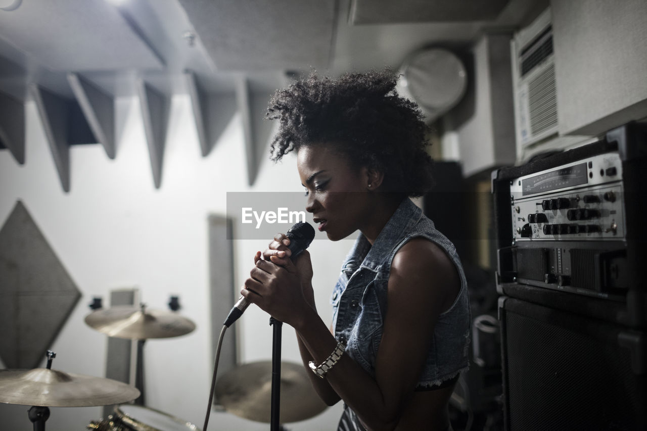 one person, indoors, real people, input device, microphone, singing, young adult, lifestyles, waist up, holding, music, singer, musician, performance, standing, casual clothing, home, curly hair, arts culture and entertainment, hairstyle