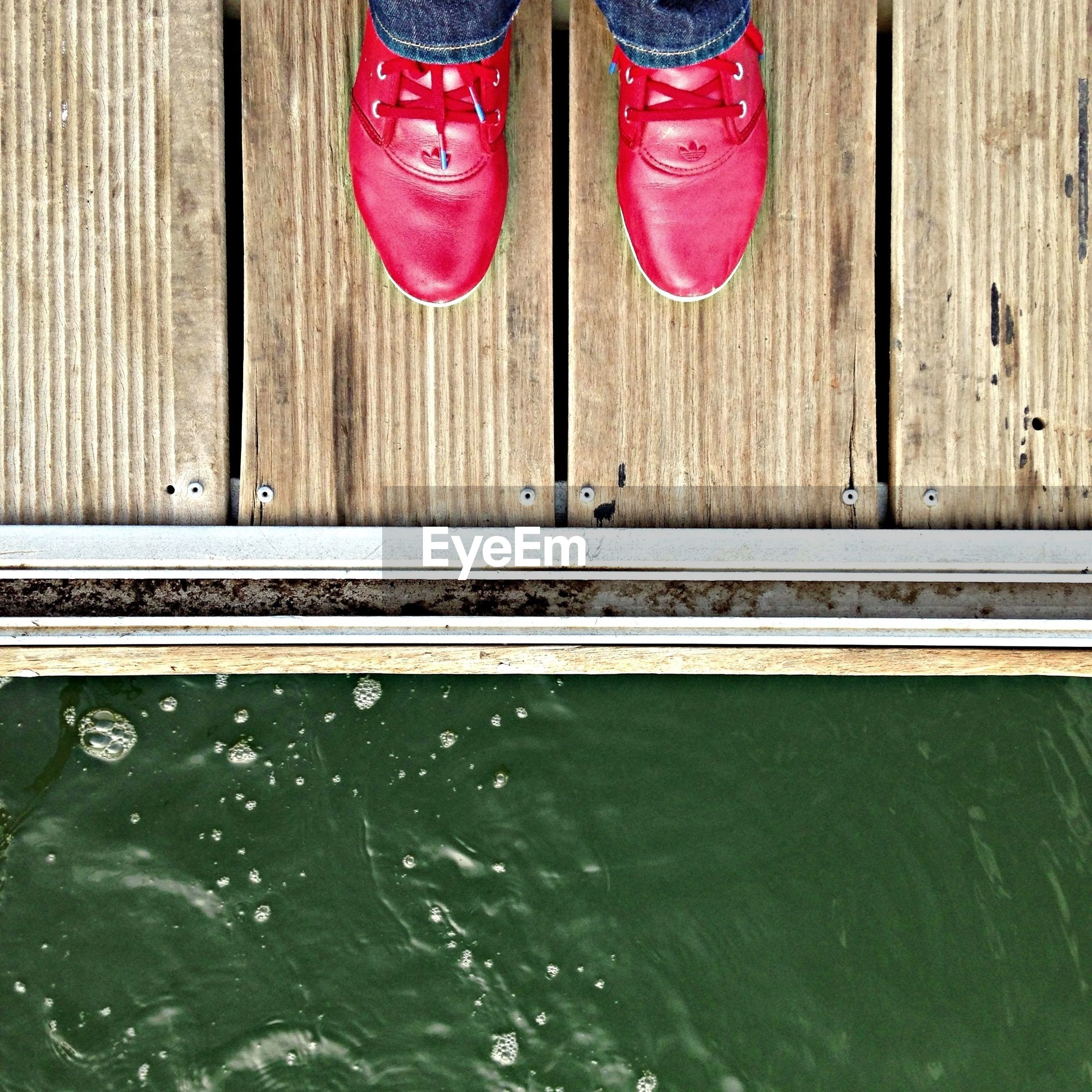 Close-up of cropped red shoes at poolside