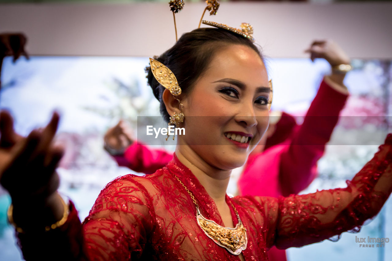 smiling, happiness, real people, celebration, traditional clothing, one person, focus on foreground, enjoyment, leisure activity, fun, lifestyles, cheerful, headshot, red, indoors, excitement, young adult, young women, day, close-up