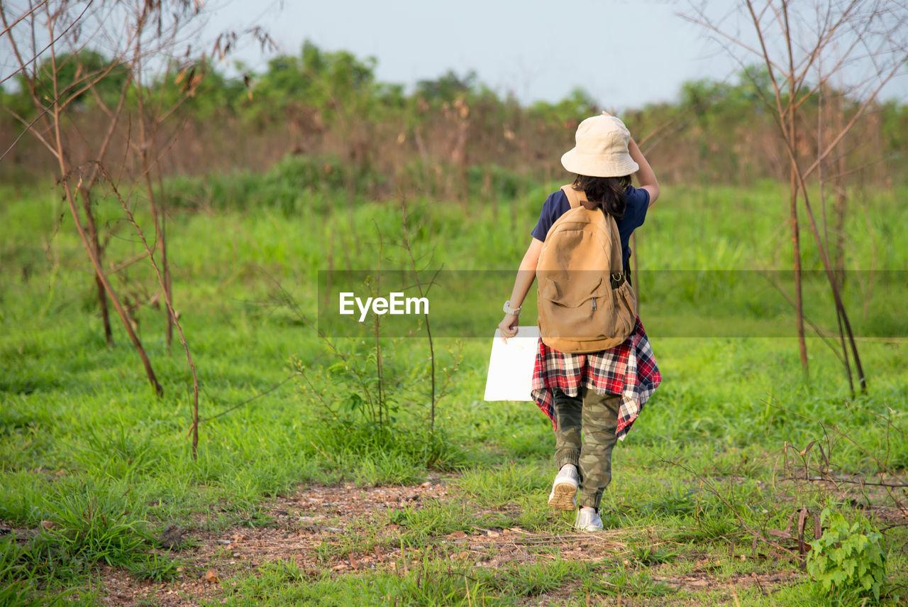 Rear view of tourist girl walking on field