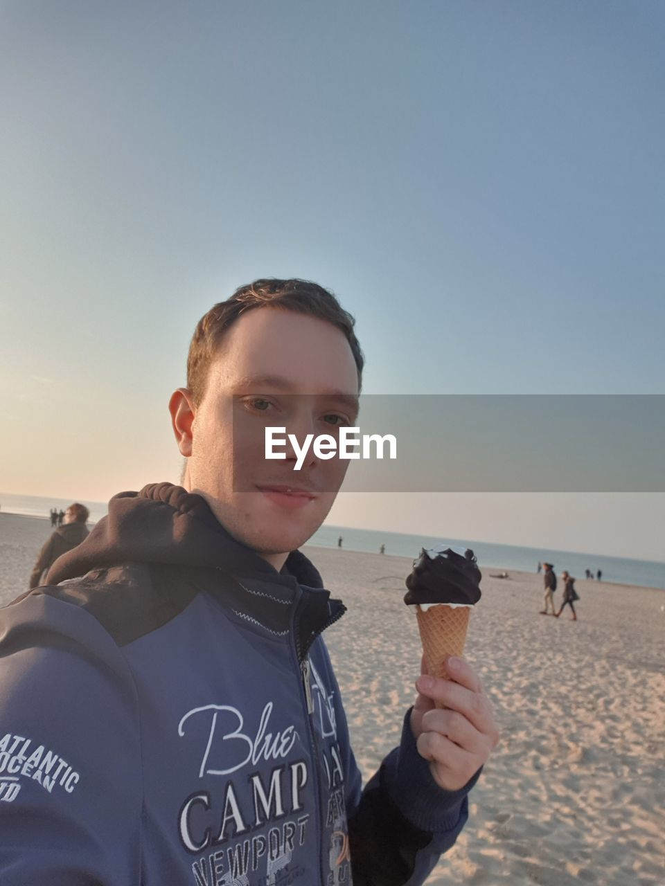 Portrait of man having ice cream at beach against clear sky