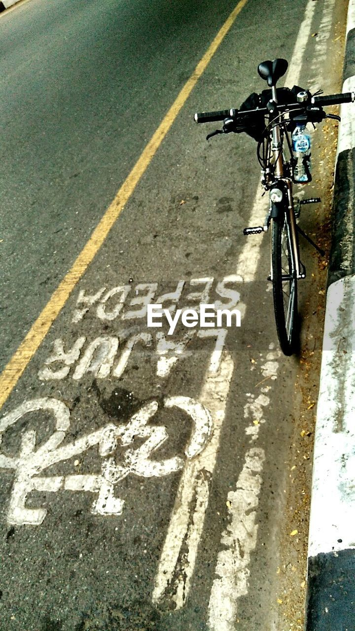 bicycle, transportation, mode of transport, text, road, land vehicle, day, no people, street, stationary, outdoors