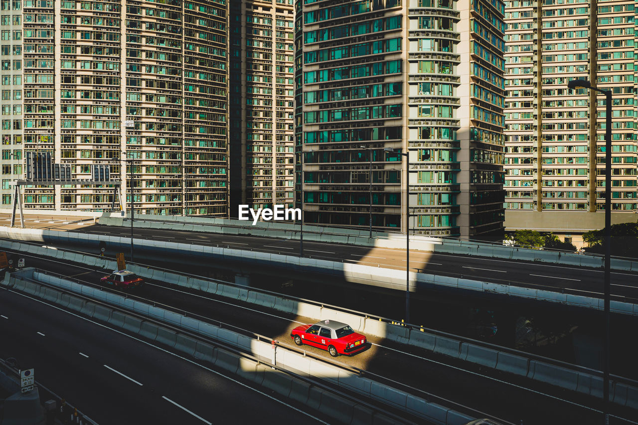 architecture, built structure, transportation, building exterior, mode of transportation, car, city, motor vehicle, land vehicle, building, road, day, no people, travel, glass - material, office building exterior, street, on the move, motion, outdoors, modern, skyscraper