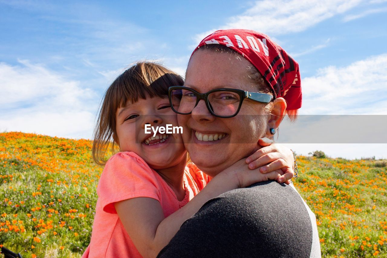 Portrait of happy mother with daughter against sky