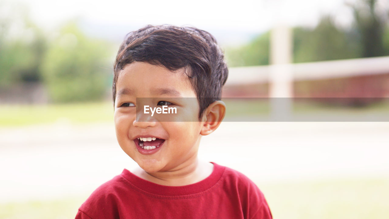 childhood, portrait, child, headshot, boys, focus on foreground, males, one person, front view, men, innocence, real people, smiling, looking at camera, day, casual clothing, cute, close-up, lifestyles, outdoors, mouth open, human face, gap toothed