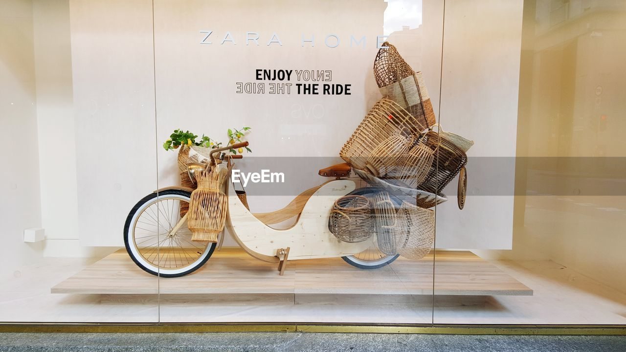 text, western script, communication, glass - material, transparent, no people, wall - building feature, indoors, wall, sign, script, non-western script, day, bicycle, still life, transportation, mode of transportation, retail, door, message