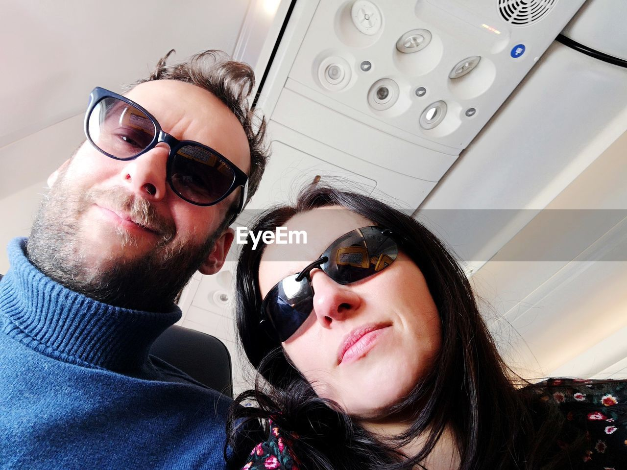 Portrait of couple wearing sunglasses in airplane