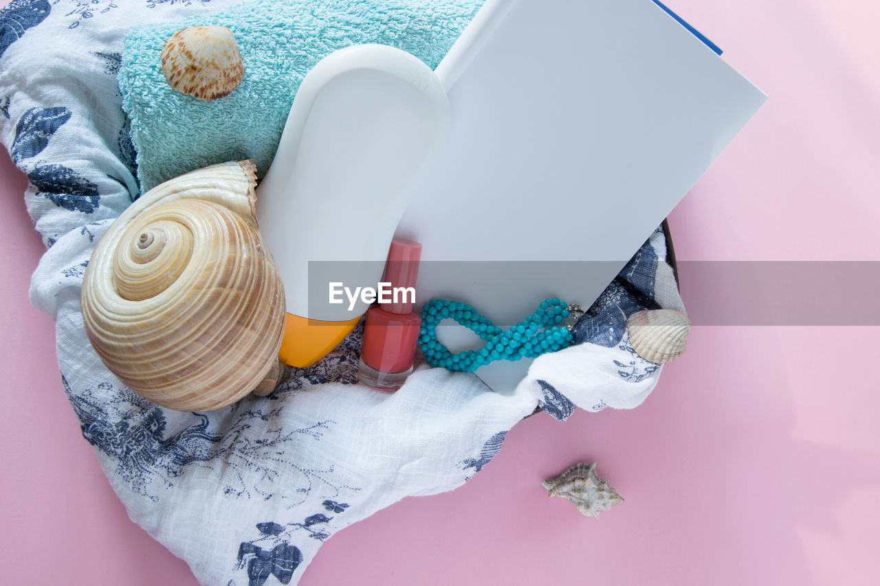 indoors, high angle view, still life, textile, no people, close-up, art and craft, wool, white color, craft, clothing, blue, multi colored, container, table, studio shot, variation, choice, rolled up