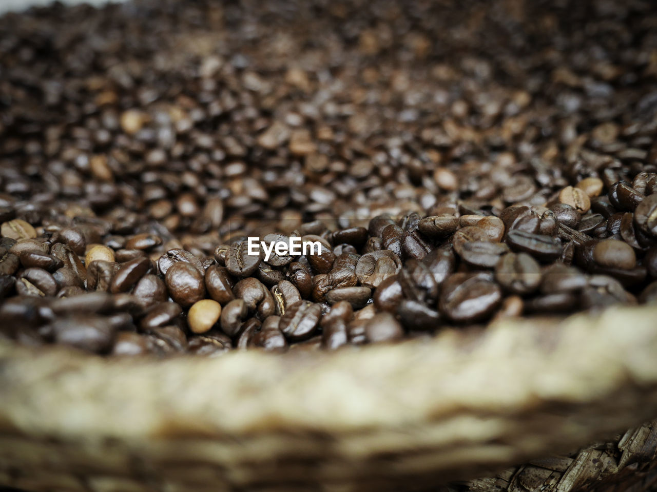 Close-up of roasted coffee beans in wicker basket in store
