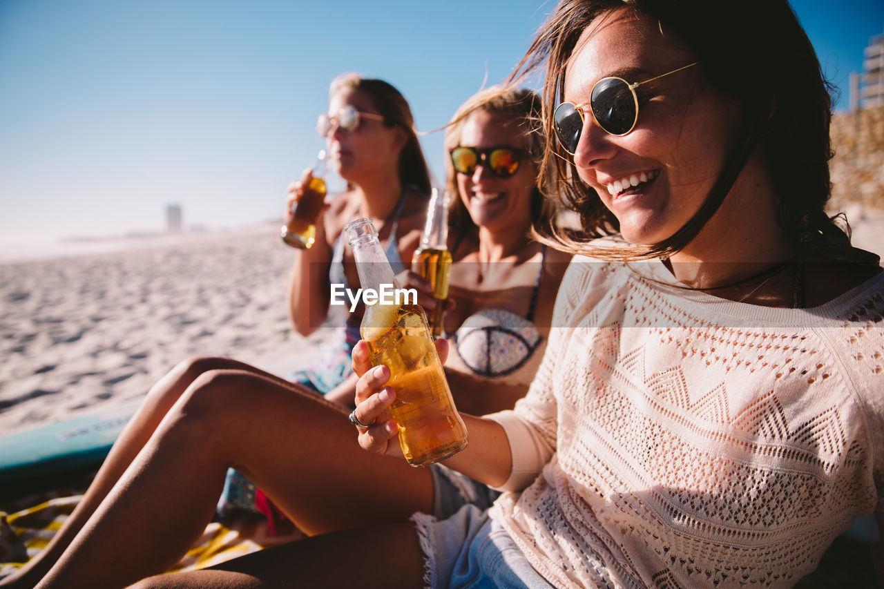 glasses, sunglasses, leisure activity, sitting, real people, young women, lifestyles, women, fashion, young adult, smiling, focus on foreground, refreshment, adult, sky, togetherness, holding, drink, friendship, drinking, outdoors