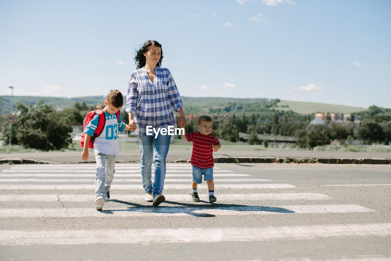 Full Length Of Mother And Children On Zebra Crossing