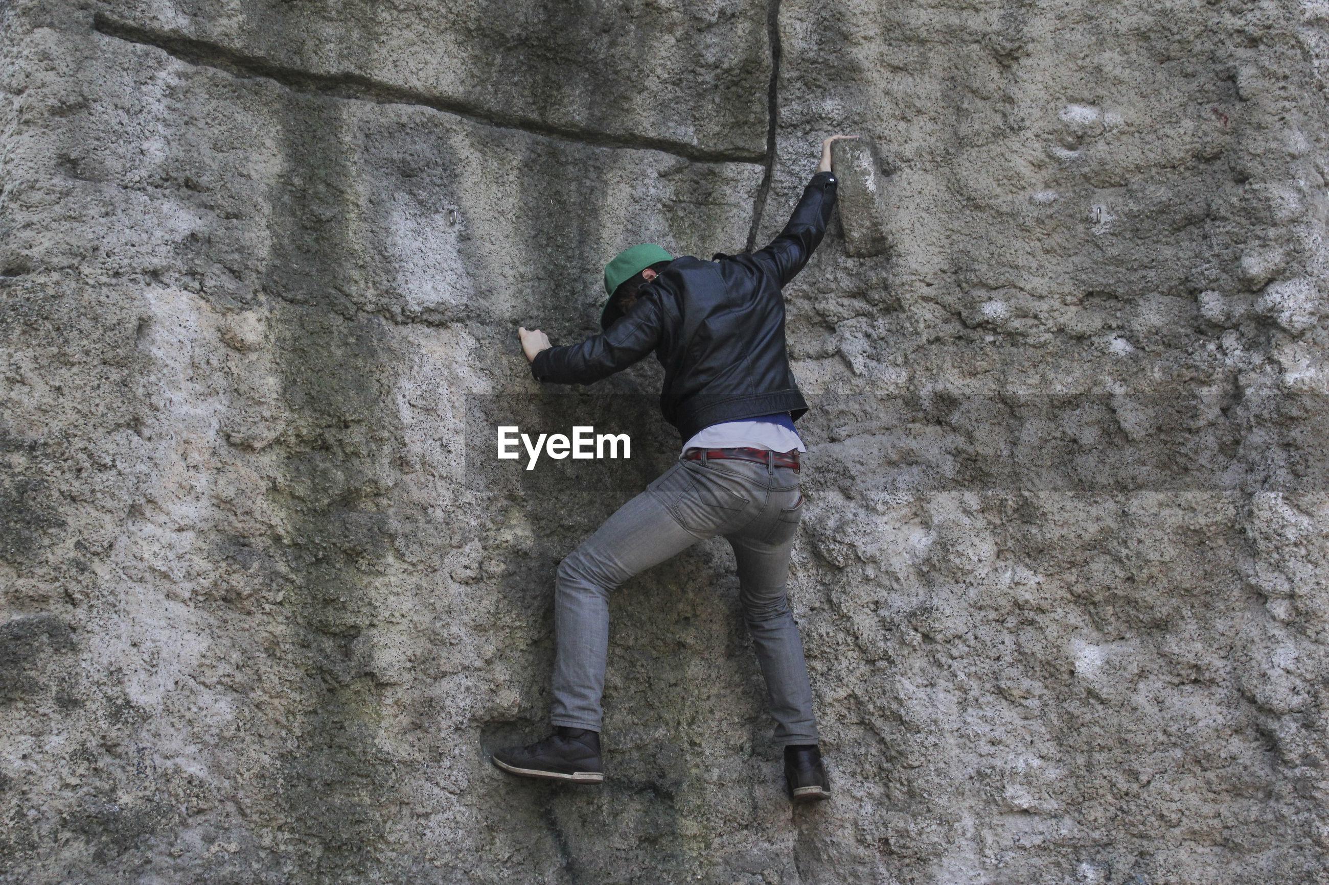 Full length of man climbing rocky mountains