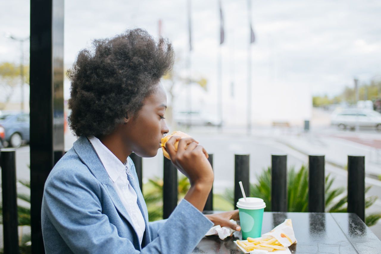 Businesswoman Holding Food And Drink At Outdoor Cafe