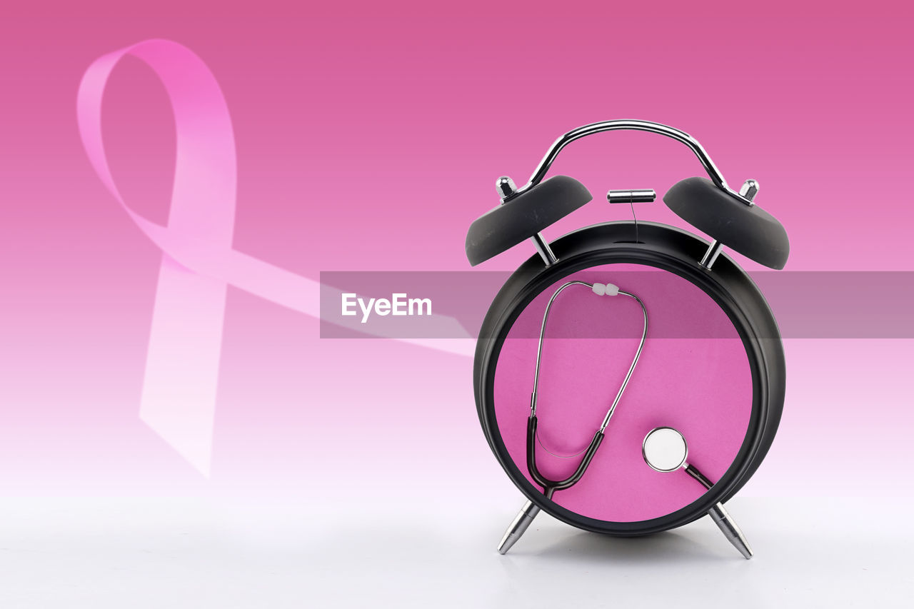 Close-up of alarm clock with stethoscope against pink background