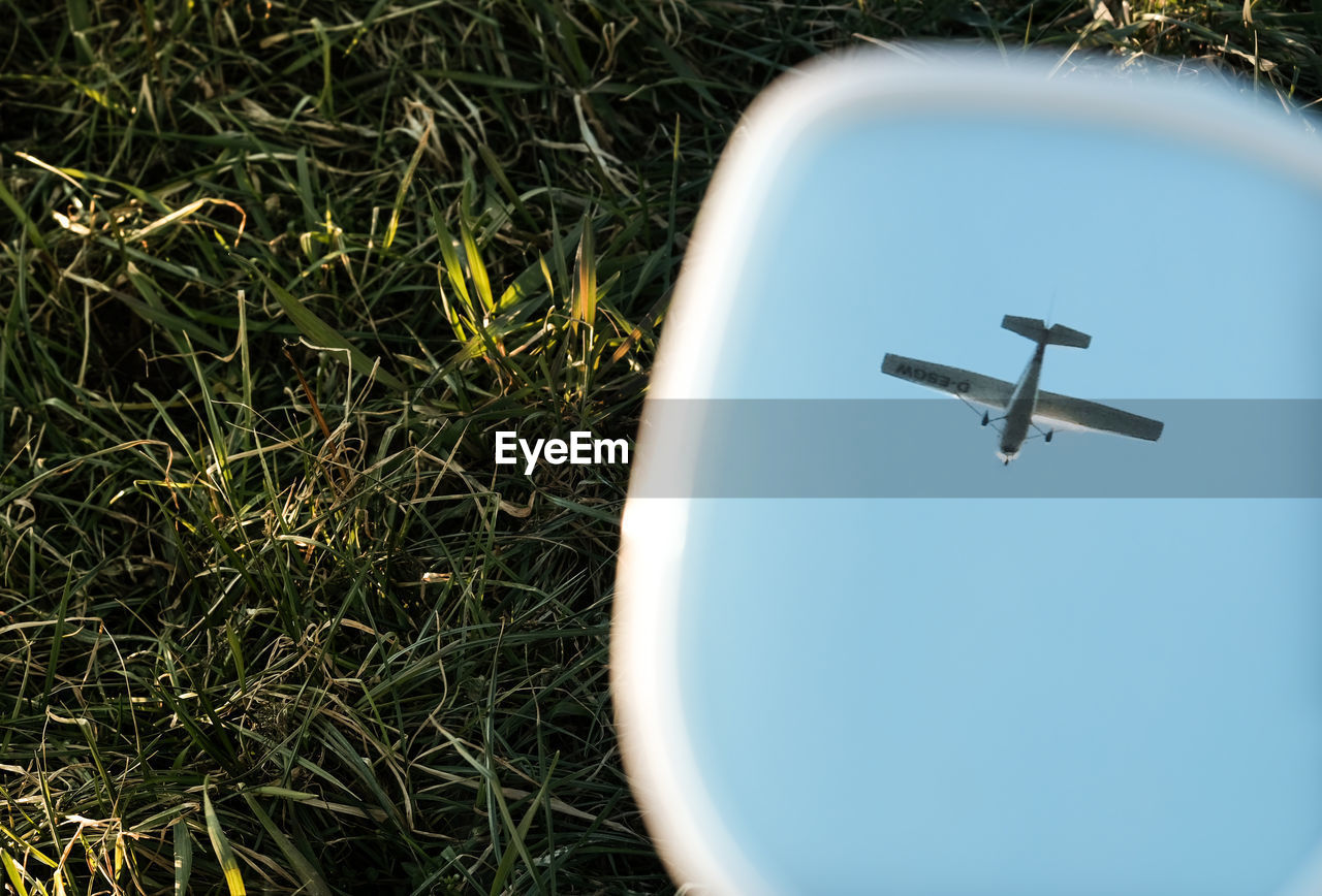 Reflection of airplane in water over field