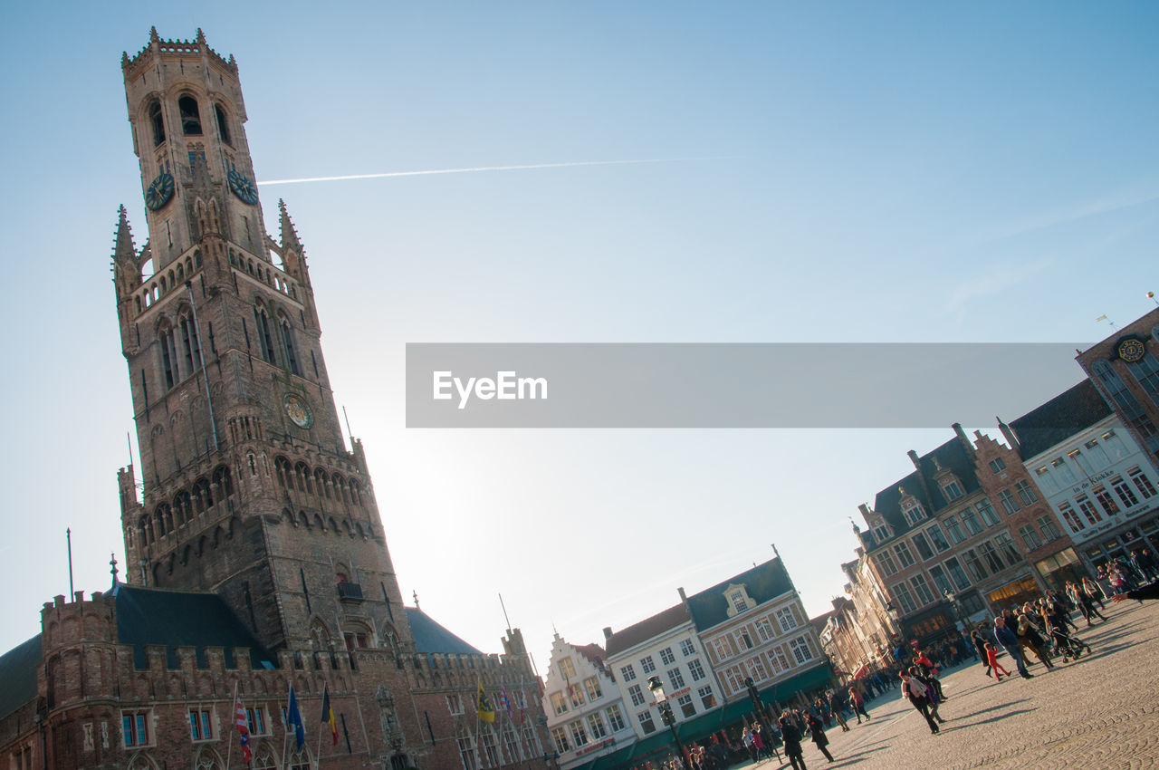 architecture, building exterior, built structure, day, low angle view, city, outdoors, travel destinations, sky, sculpture, spirituality, clear sky, statue, clock tower, large group of people, people