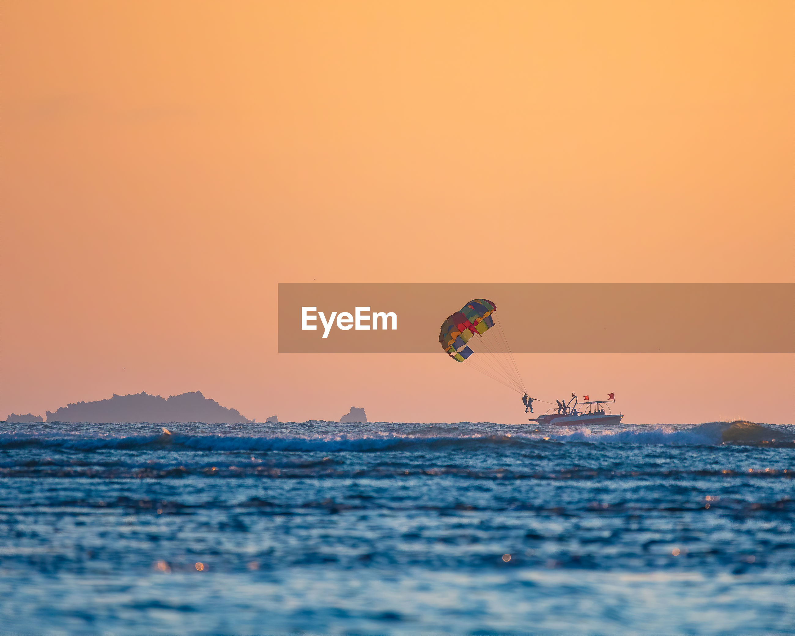 PEOPLE IN SEA AGAINST SKY DURING SUNSET