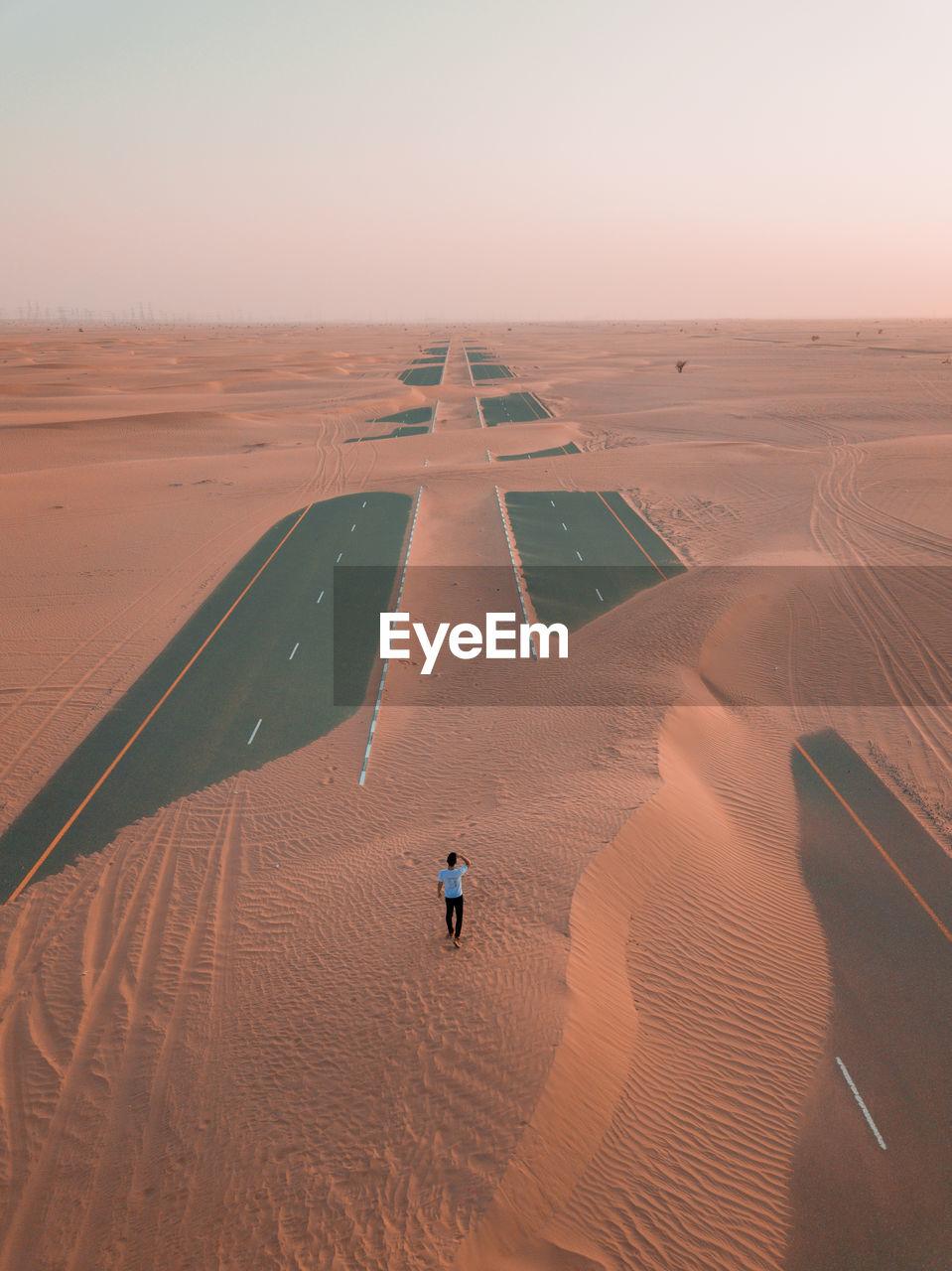 Man Walking On Desert Against Sky