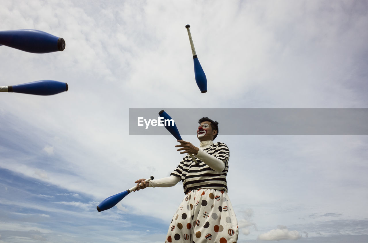 Low Angle View Of Clown Standing Against Sky