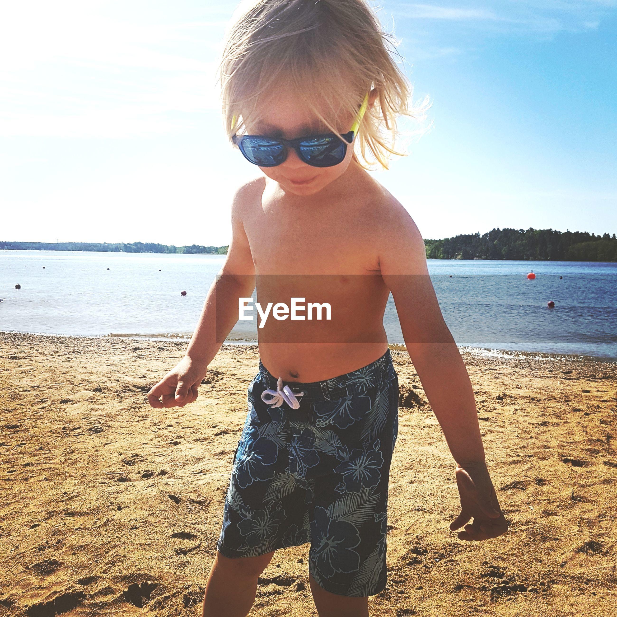 Cute boy wearing sunglasses at beach against sky