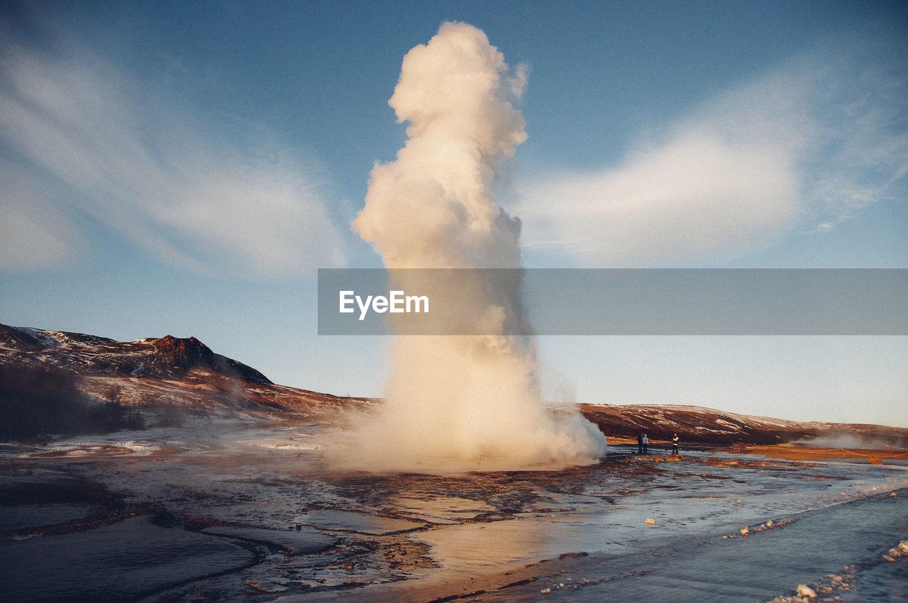 Geyser erupting against sky