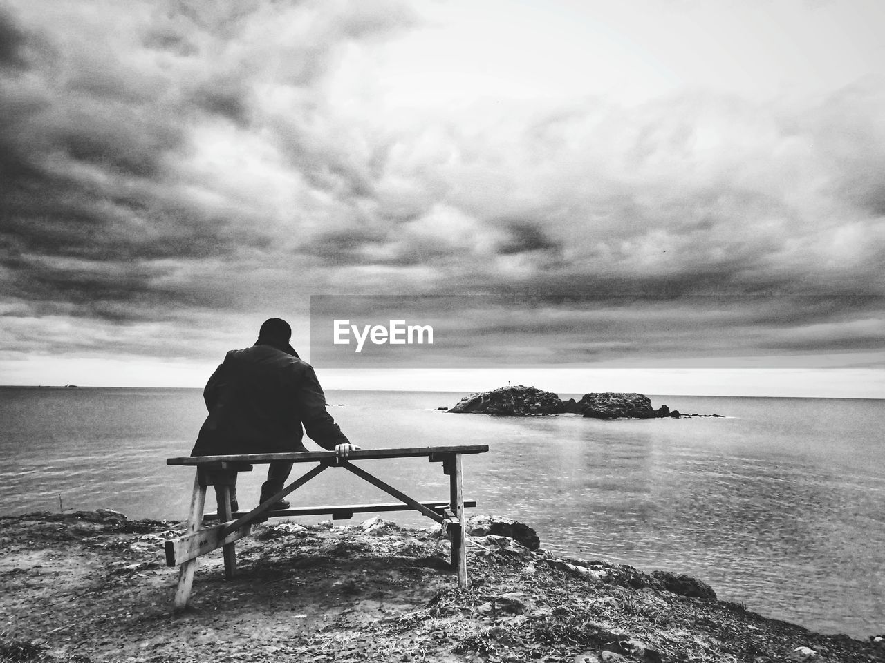 rear view, sky, water, cloud - sky, sitting, sea, one person, beauty in nature, scenics - nature, nature, beach, men, tranquility, tranquil scene, land, real people, seat, horizon over water, horizon, looking at view, outdoors, contemplation