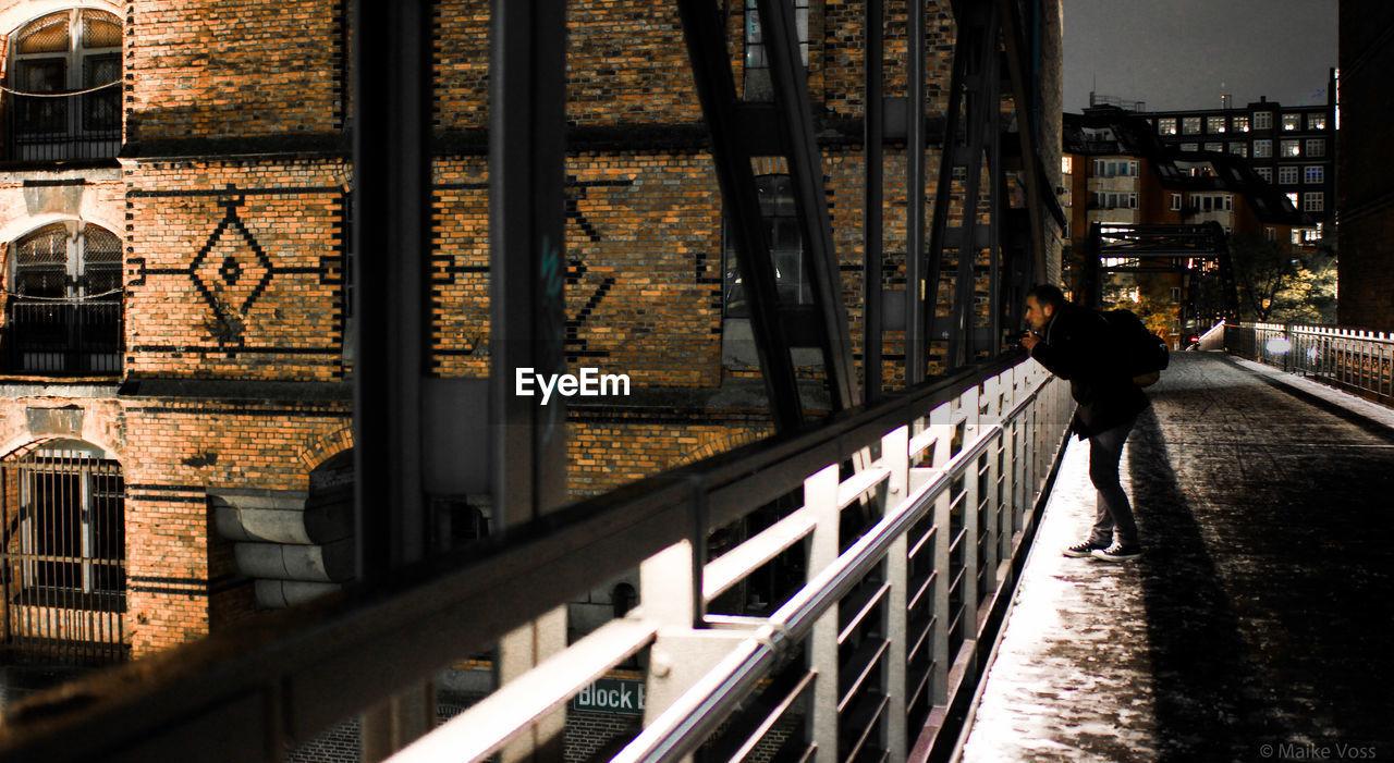 Man on bridge in city