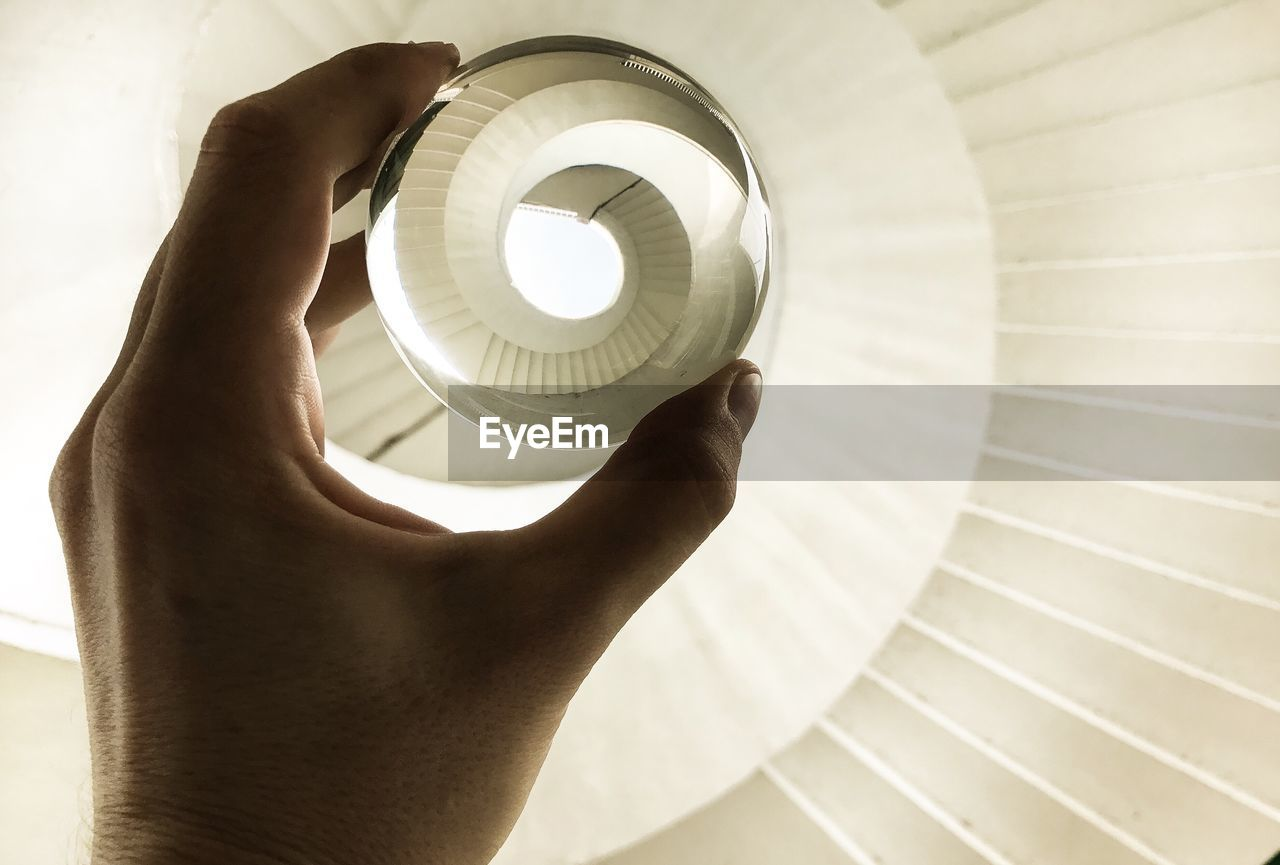 Cropped Hand Of Woman Holding Crystal Ball Over Spiral Staircase